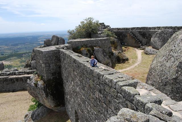 Vista de las murallas del castillo de Monsanto con un niño subido en lo alto