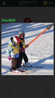 Двое детей держатся за палку впереди и едут на лыжах за ней