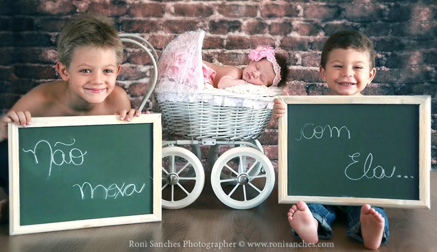 newborn com irmãos segurando placa