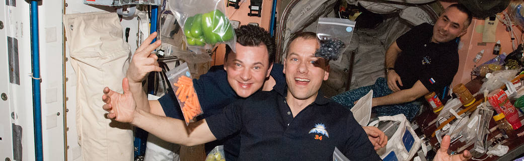 people and baggies of food floating in the space station