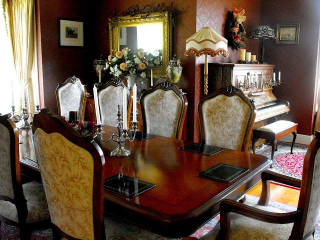 Antique Victorian dining table, chairs and piano in dining room