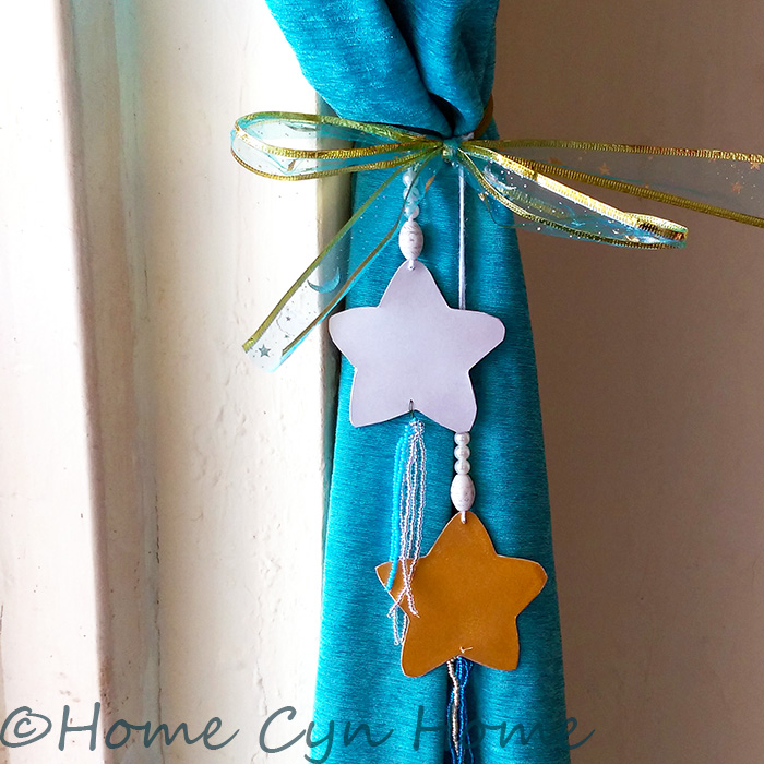 Give a pretty makeover to your curtains with these card stock stars and glass beads tassels.