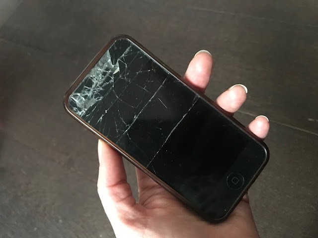 An iPhone 5 held in a hand with sellotape keeping the smashed glass together