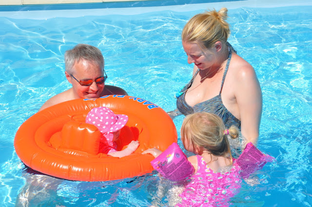 Me and G in the swimming pool with M in arm bands and pink swimsuit and Little in a floating baby ring