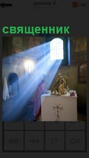 В помещении церкви стоит священник и поток света через окно падает освещая помещение