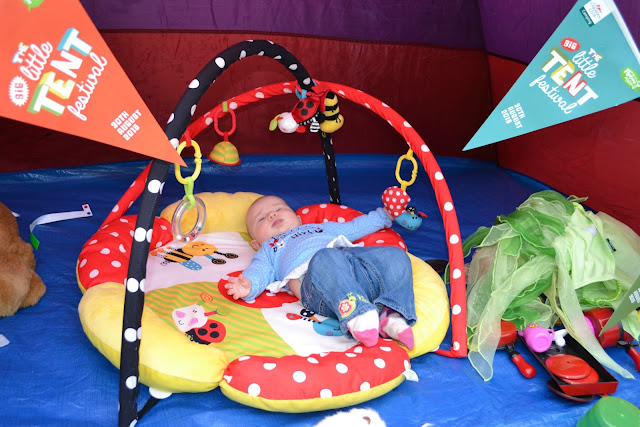 Tin Box Baby on a play mat in a tent