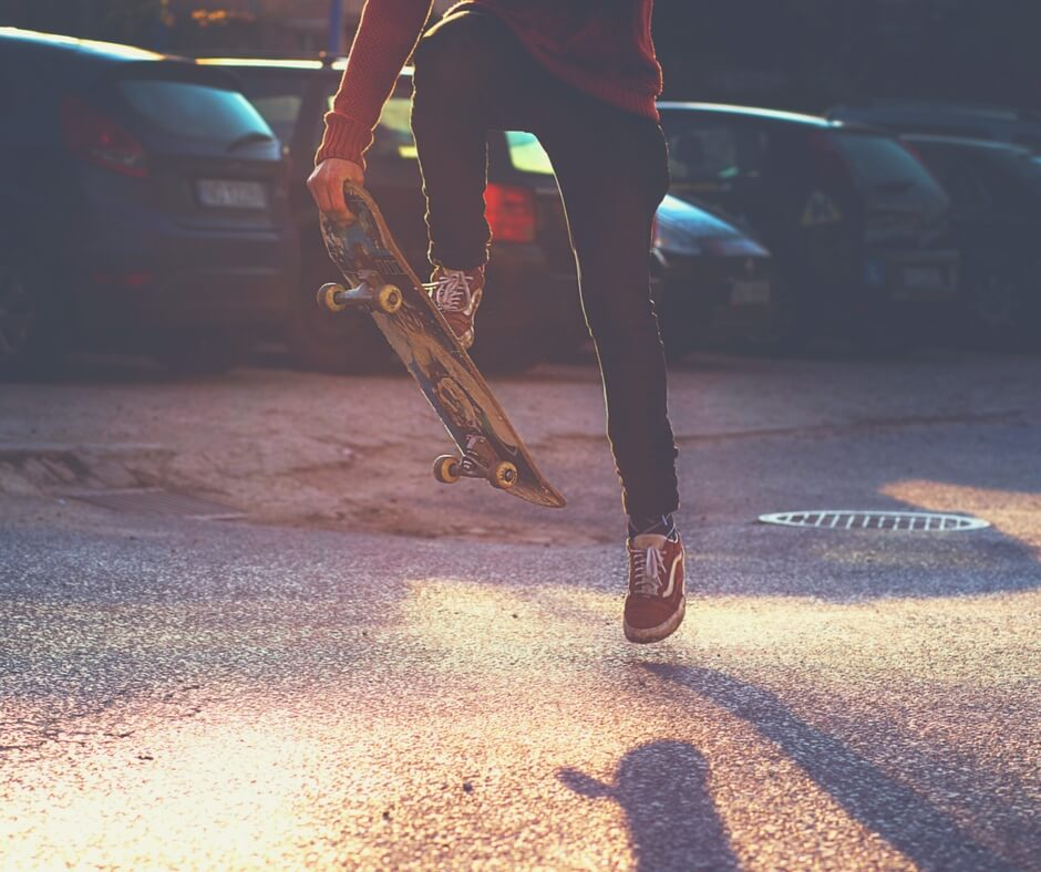 "A teenage boy wearing red trainers with white laces does a skateboard jump. The photo is just of his legs and skateboard. The boy holds the skateboard in the air with one foot on it, the other is hovering just above the concrete of the car park. Blurred cars parked in a line in the background. The sun is setting, shining down and leaving long shadows on the ground. Image for ""Teaching your children about online privacy"""