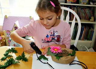 "Tessa remembered a sack of abandoned faux flowers in our basement that she decided to use to craft her ""All About Me"" nest. She learned how to use a hot glue gun at the fall camporee she attended a couple of weeks ago, so I let her have at it. This was her first time doing something like this, so I provided some pointers on floral arrangement along the way."