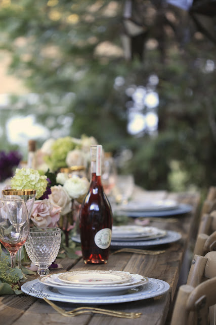 rustic table setting outdoors with vintage plates and flowers