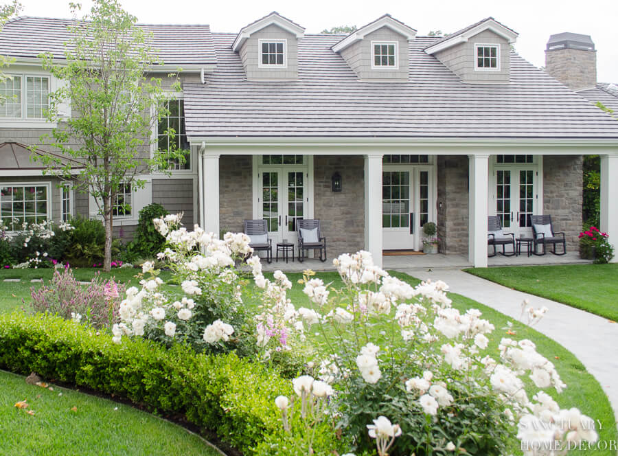 farmhouse style home with stone accents and taupe shingle siding