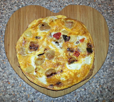 An omelette displayed on a heart shaped chopping board