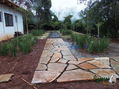 Execução do caminho de pedra no jardim com pedras Goiás com execução do paisagismo com mudas de moréais em residência em Piracaia-SP.