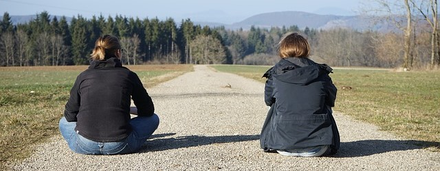Two Girlfriends Sitting on Opposite Sides of the Road