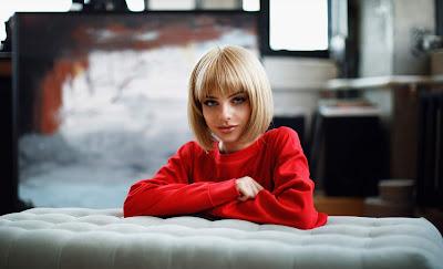 Chica rubia con pelo corto y suéter rojo mirando a cámara