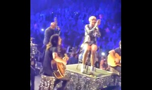Rather than depart, Miley Cyrus filming fight fans in the audience
