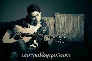 Foto Giorgino Abraham sedang bermain Gitar