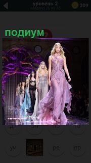 На подиуме проходят девушки, демонстрируя модную одежду
