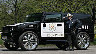 County mounty by a Hummer police car