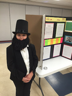 Child dressed in black hat, white shirt and black jacket like Abraham Lincoln