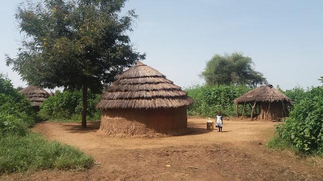 little girl standing by a hut