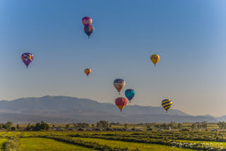 Cramer Imaging's fine art photograph of lots of hot air balloons taking flight in Panguitch Utah over a farm field and mountains