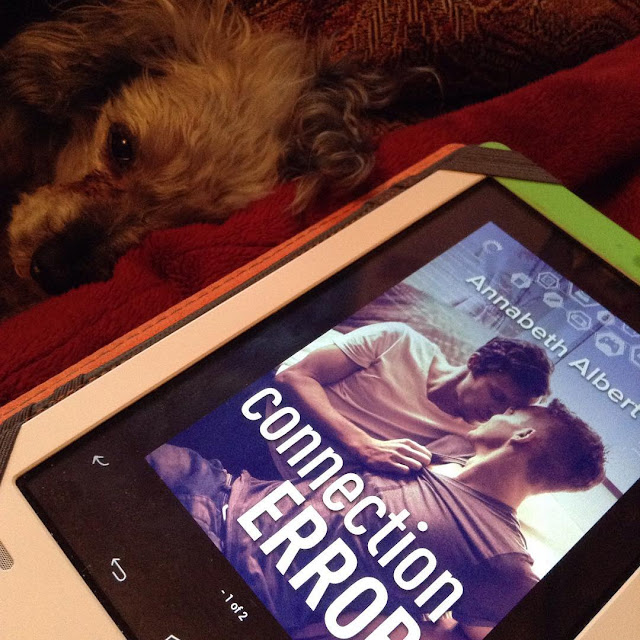 Murchie curls up on his side on his red blanket. His visible eye looks straight at the camera. In front of him is a white Kobo with Connection Error's purple-tinged cover on its screen. It features two white guys about to kiss.