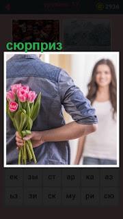 мужчина за спиной спрятал цветы в качестве сюрприза для женщины