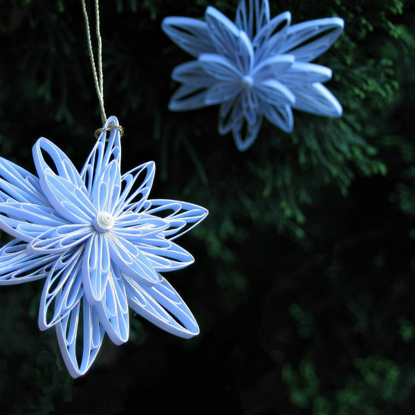Two Quilled Snowflake Ornaments hanging on green foliage