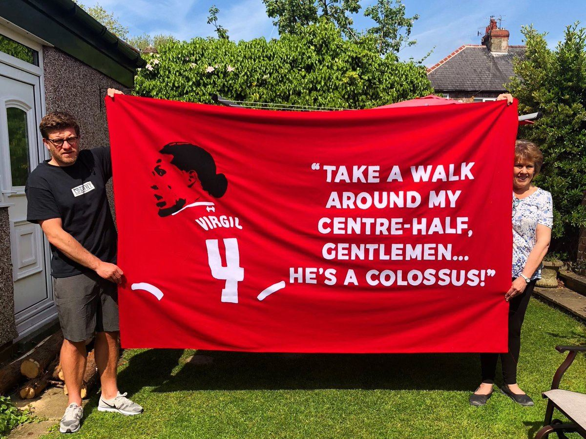 Two Liverpool fans show their home made Virgil Van Dijk is a colossus banner