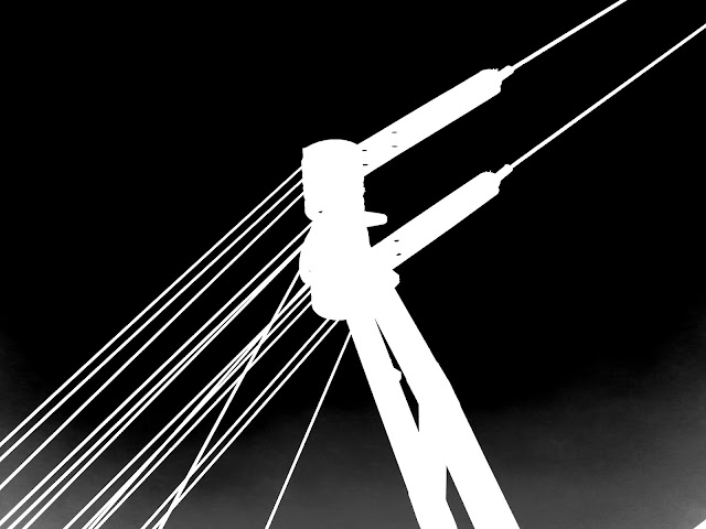 Part of a crane and its cables. Inverted black and white.