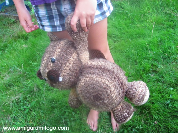 child holding stuffed beaver by arm