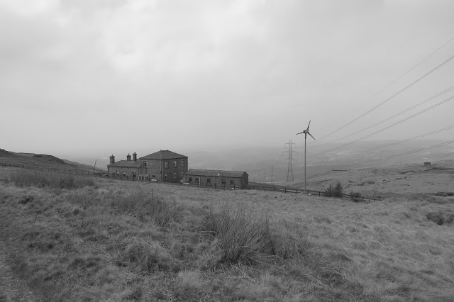 A black and white photo of a farm and a small wind generator. Wires and a line of pylons disappear into the haze of the valley.