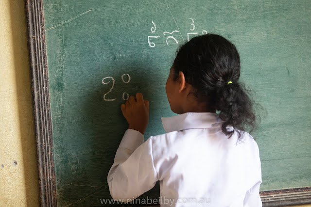 Female Cambodian Child writes on the blackboard in Khmer