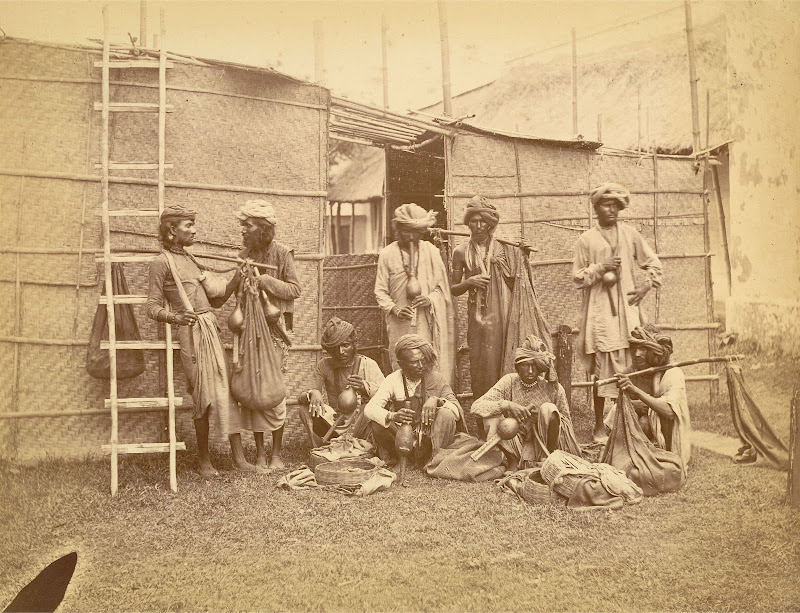 Portrait of Nine Snake Charmers Posed with their Pipes, Baskets and Sacks Containing the Snakes - Eastern Bengal 1860's