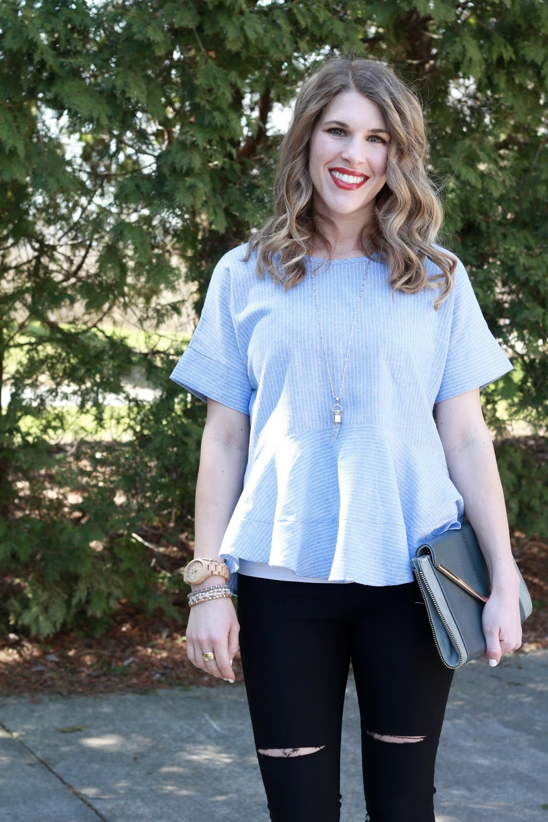 blue striped peplum top, distressed black jeans, black heels, grey envelope clutch