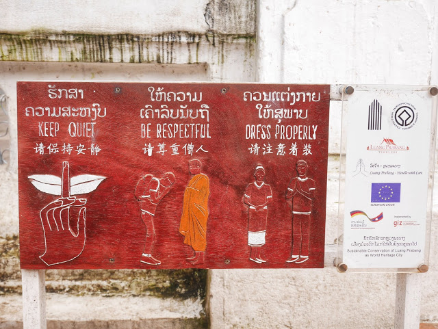 a sign informing travelers how to behave at a Buddhist temple in Luang Prabang, Laos