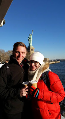 Image of a young couple wearing warm winter clothing holding hot drinks on a boat in front of the statue of liberty in New York