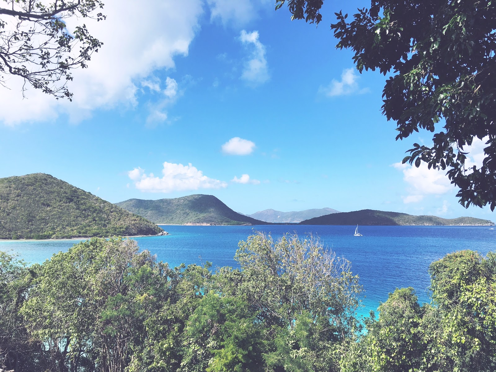 View from St. John turquoise Caribbean Sea waters, sail boat, green mountains