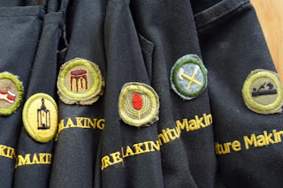Aprons hanging with Boy's Brigade Badges stitched on.