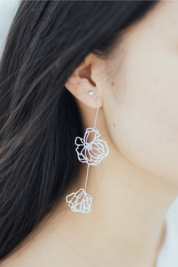 paper cut white floral drop earrings on model
