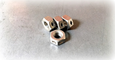 Stainless Steel Custom Hex Nuts With A Hole Drilled Through One Corner - 1/4-28 Thread