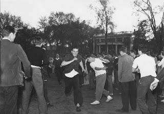 A photograph of a crowd of men outside, some running.