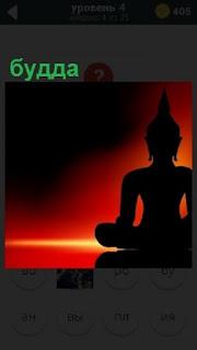 В свете красного заката на постаменте стоит статуя будды