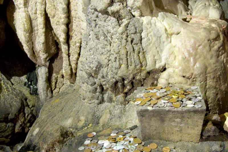 coins offered at a small shrine within cave