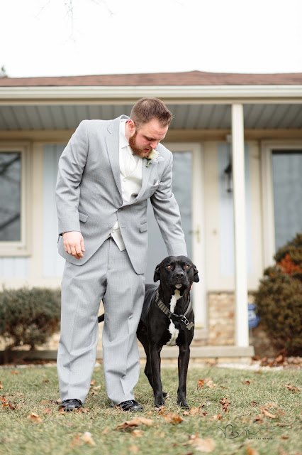 groom getting ready for wedding with dog