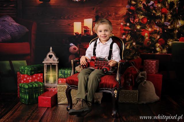 mały piotruś z samochodzikiem pozuje na tle świątecznym