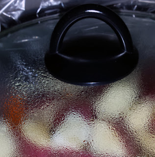 A clear crock pot lid with condensation on the inside. Cut up red potatoes are visible.