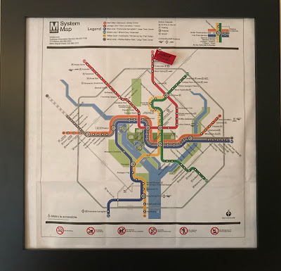 Metro system map in a frame with a red flag stuck into Forest Glen with a date and mileage on it