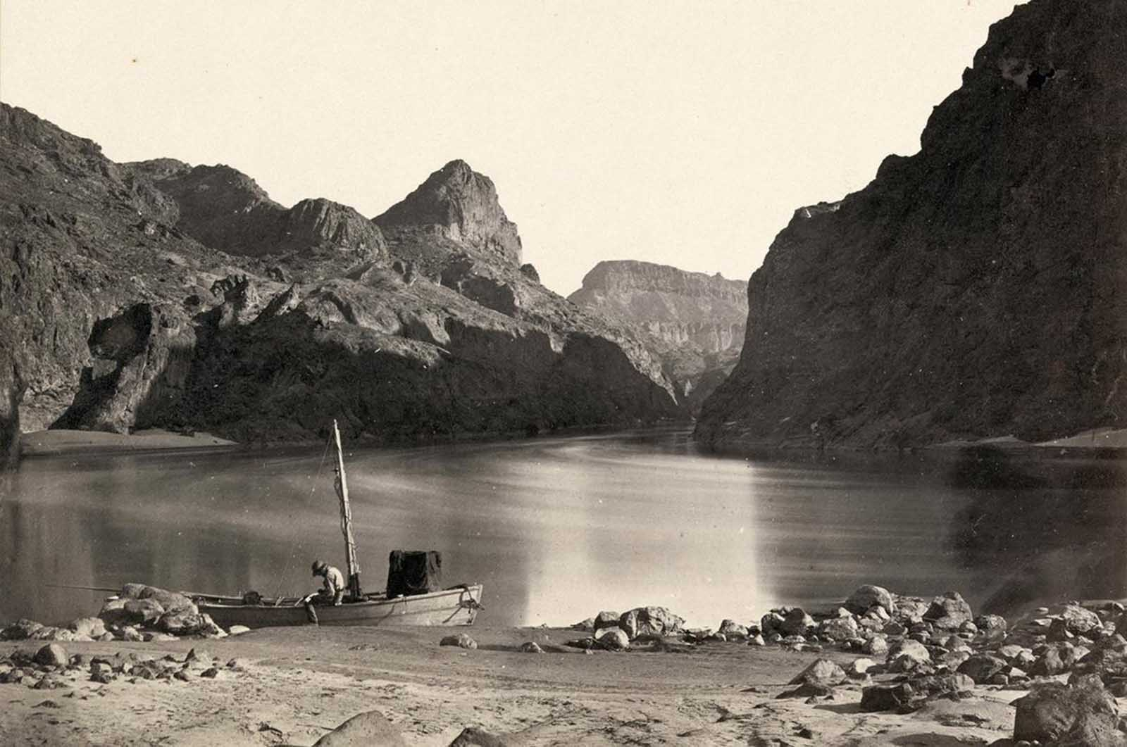 A man sits in a wooden boat with a mast on the edge of the Colorado River in the Black Canyon, Mojave County, Arizona. At this time, photographer Timothy O'Sullivan was working as a military photographer, for Lt. George Montague Wheeler's U.S. Geographical Surveys West of the One Hundredth Meridian. Photo taken in 1871, from expedition camp 8, looking upstream.