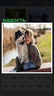 На скамейке сидят собака и мальчик, который с радостью обнимает друга